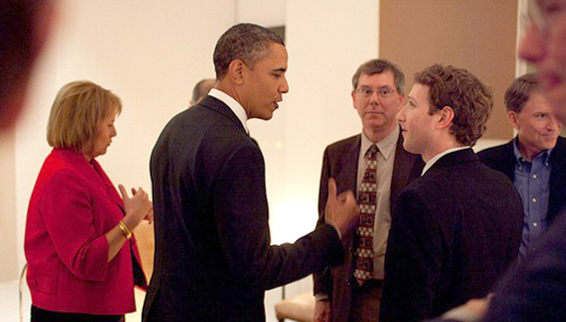 Mark Zuckerberg in a suit talking with President Obama